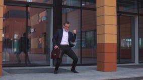 跳舞在商业中心附近的年轻英俊的商人在手上拿着公文包 慢的行动 股票视频