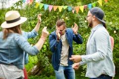 跳舞在夏天的愉快的朋友在庭院里集会 免版税库存照片