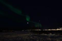 跳舞在多雪的领域的极光borealis在与满月的海岸附近 免版税库存图片