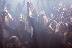 跳舞在夜总会的快乐的爱好者在音乐节期间 免版税库存图片