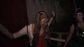 跳舞在夜总会的服装的两个女孩在万圣夜期间集会 股票录像