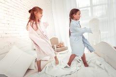 跳舞在床上的逗人喜爱的活跃女孩 库存图片
