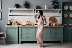 跳舞在早晨的睡衣的少女在厨房 免版税库存图片