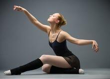 跳舞在有被伸出的胳膊的地板芭蕾舞女演员 免版税库存照片