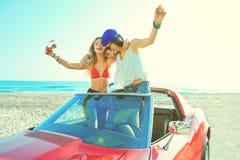 跳舞在海滩的一辆汽车的美丽的女招待 免版税库存图片