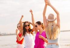 跳舞在海滩的小组微笑的妇女 免版税库存图片
