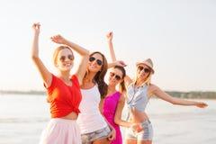 跳舞在海滩的小组微笑的妇女 免版税图库摄影