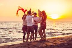 跳舞在海滩的青年人在日落 库存照片