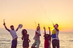 跳舞在海滩的青年人在日落 图库摄影
