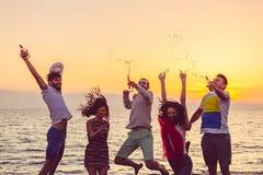 跳舞在海滩的青年人在日落 库存图片