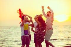 跳舞在海滩的青年人在日落 免版税库存照片