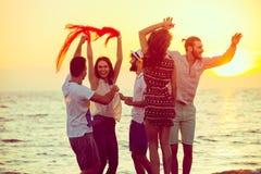 跳舞在海滩的青年人在日落 免版税库存图片