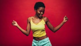 跳舞在红色背景的非洲妇女 免版税库存图片