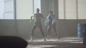 跳舞在被放弃的大厦的大窗口前面的两个男孩 同时采取舞蹈行动的少年 人 股票录像