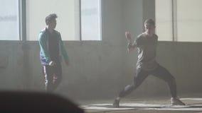 跳舞在被放弃的大厦的大窗口前面的两个男孩 同时采取舞蹈行动的少年 人 股票视频
