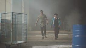 跳舞在被放弃的大厦黑暗和多灰尘的屋子的两年轻人  同时采取舞蹈行动的少年 股票视频