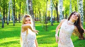 跳舞在被日光照射了桦树树丛里的相似的服装的白肤金发和深色的妇女 股票录像