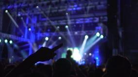 跳舞在闪烁光,挥动的手的音乐会的激动的音乐迷 股票视频