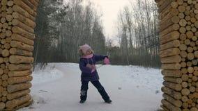 跳舞在雪的小女孩滑稽的舞蹈在冬天步行期间在森林里 股票视频