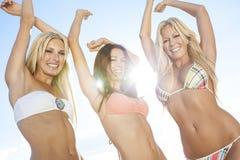 跳舞在晴朗的海滩的比基尼泳装的三名美丽的妇女 库存照片