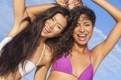 跳舞在晴朗的海滩的比基尼泳装的两名美丽的妇女 免版税图库摄影