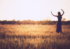 跳舞妇女模糊的剪影反对日落天空的 免版税库存图片