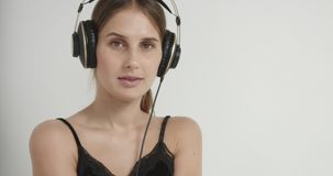 跳舞对在耳机的音乐的内衣的逗人喜爱的女孩 股票录像