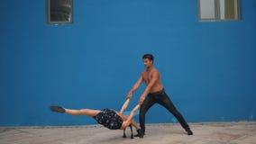 跳舞展示与杂技的伙伴肉欲的舞蹈样式在蓝色背景的慢动作 跳舞户外 股票视频