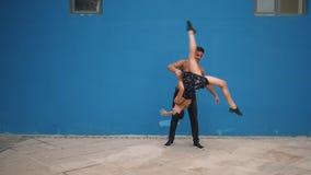 跳舞展示与杂技的伙伴肉欲的舞蹈样式在蓝色背景的慢动作 跳舞户外 股票录像