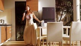 跳舞愉快的年轻女人获得乐趣唱歌和在有磨丝器的厨房,当做早餐3840x2160时 股票视频