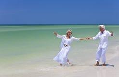 跳舞愉快高级热带的海滩夫妇 免版税库存照片