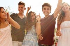 跳舞户外反对太阳的小组少年朋友 免版税库存照片