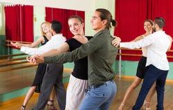 跳舞探戈的三对愉快的夫妇 免版税库存照片