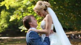 跳舞新婚佳偶在晴朗的公园 英俊的新郎在天空中转动他的年轻人微笑的白肤金发的新娘 影视素材