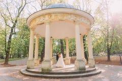 跳舞新婚佳偶在晴朗的公园安置的老凹室 免版税图库摄影