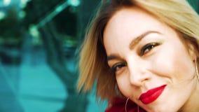 跳舞有看照相机的红色口红的白肤金发的妇女特写镜头画象  股票录像