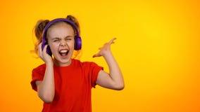 跳舞滑稽的十几岁的女孩听到在耳机的音乐和,喜爱的歌曲 免版税图库摄影