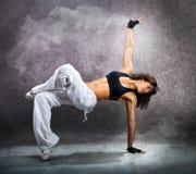 跳舞现代舞节律唱诵的音乐的年轻美丽的运动妇女 免版税库存照片