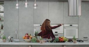 跳舞的年轻女人在厨房里,当做早餐愉快的移动和制造的滑稽的面孔,拿着手搅拌器时 影视素材