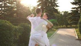 跳舞缓慢的华尔兹的愉快的年轻爱恋的夫妇在日落在公园 股票视频
