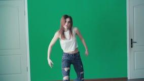 跳舞节律唱诵的音乐的年轻俏丽的女孩在4K的舞蹈演播室 股票录像