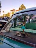 跳舞草裙舞女舞伴在一辆经典汽车的窗口里 免版税库存照片