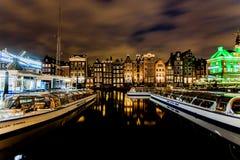 跳舞议院和小船在Damrak在晚上在阿姆斯特丹 免版税库存图片