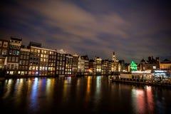 跳舞议院和小船在Damrak在晚上在阿姆斯特丹 库存照片