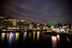 跳舞议院和小船在Damrak在晚上在阿姆斯特丹 库存图片