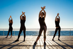 跳舞zumba的嬉戏女孩剪影在海附近在日出 图库摄影