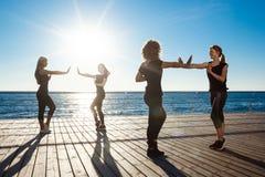 跳舞zumba的嬉戏女孩剪影在海附近在日出 免版税库存图片