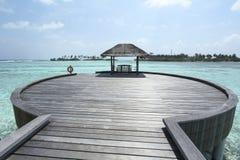 跳船和小船靠码头与清楚的蓝色热带wate在Mldives 免版税库存照片