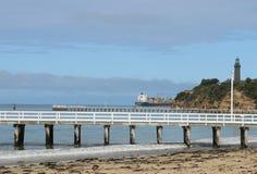 跳船和海滩与货船和灯塔在背景中 库存图片