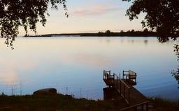 跳船在寂静的水中反射了在日落,在跳船的湿脚印 图库摄影